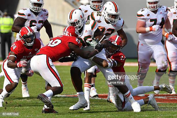 David Njoku of the Miami Hurricanes runs with the ball against Jack Tocho and Josh Jones of the North Carolina State Wolfpack at CarterFinley Stadium...