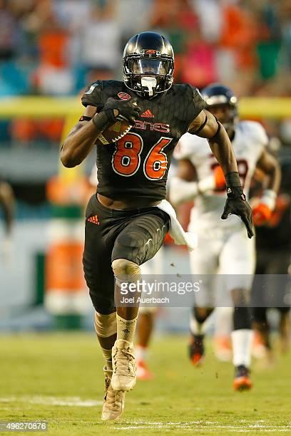 David Njoku of the Miami Hurricanes runs with the ball against the Virginia Cavaliers on November 7 2015 at Sun Life Stadium in Miami Gardens Florida...
