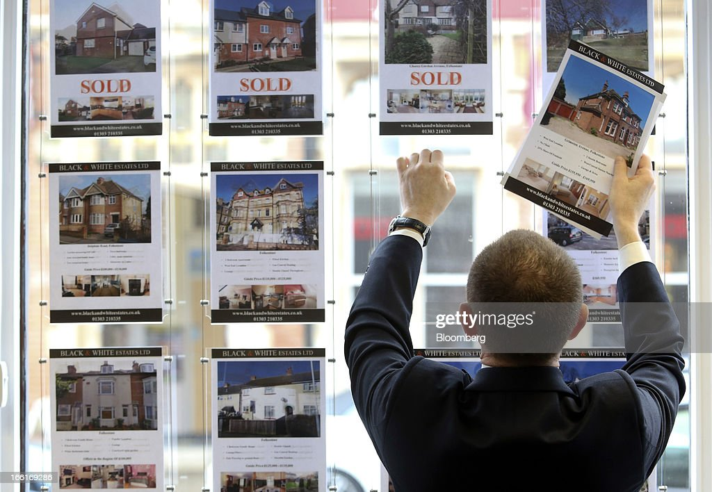 David Nutley an estate agent is seen placing a 'For Sale' advert in the window of the estate agents office in this arranged photograph in Folkestone...