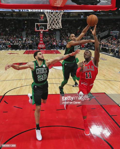 David Nwaba of the Chicago Bulls drievs to the basket against Abdel Nader and Al Horford of the Boston Celtics at the United Center on December 11...
