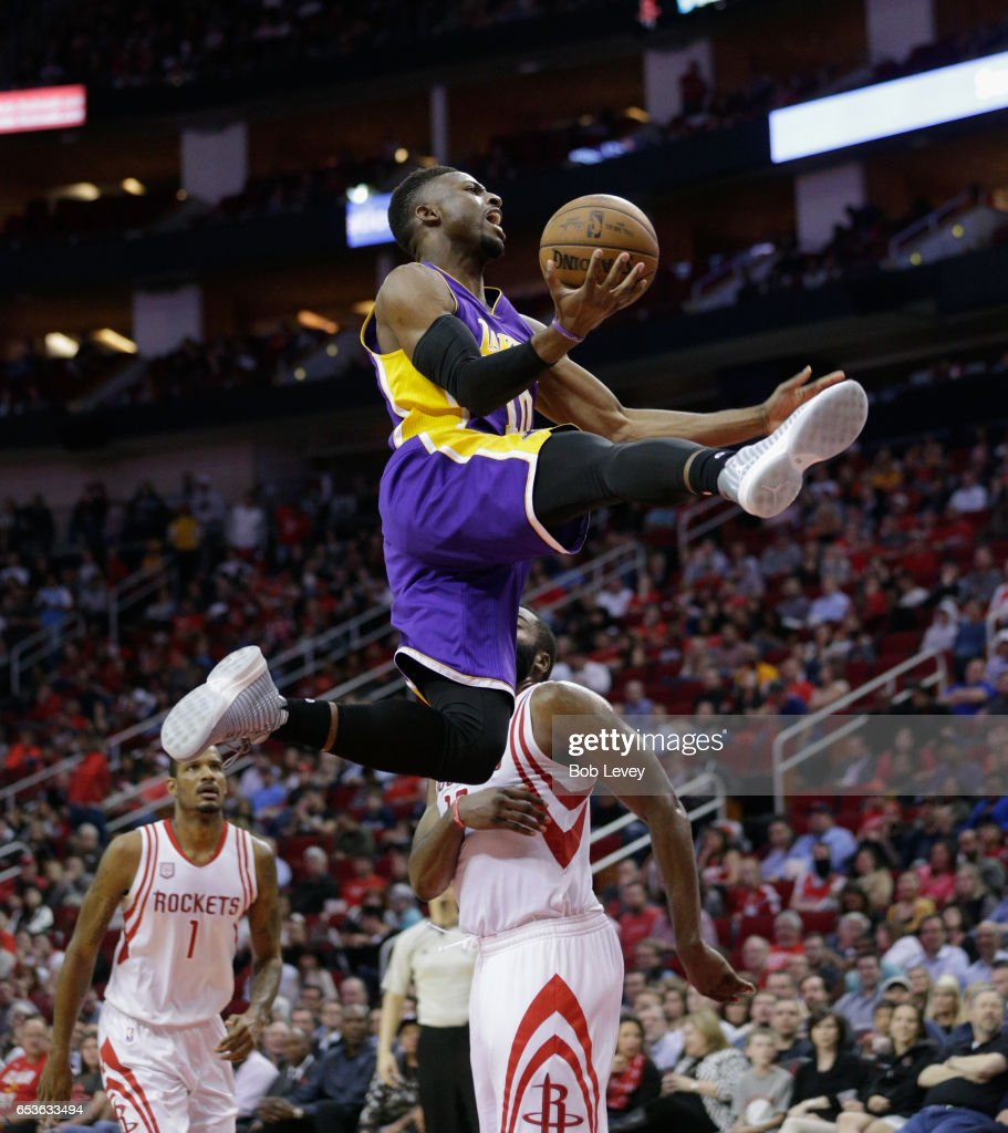 David Nwaba #10 of the Los Angeles Lakers drives past James Harden #13 of the Houston Rockets and Trevor Ariza #1 during the fourth quarter at Toyota Center on March 15, 2017 in Houston, Texas.