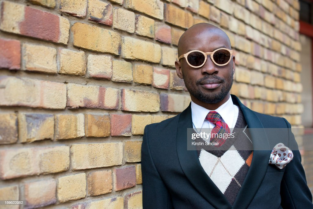 David Nyanzi photographer wearing an H and M sweater, a Dolce and Gabbana jacket, vintage tie and pocket scarf, Hugo Boss shirt and Finlay and Co sunglasses on day 3 of London Mens Fashion Week Autumn/Winter 2013, on January 09, 2013 in London, England.