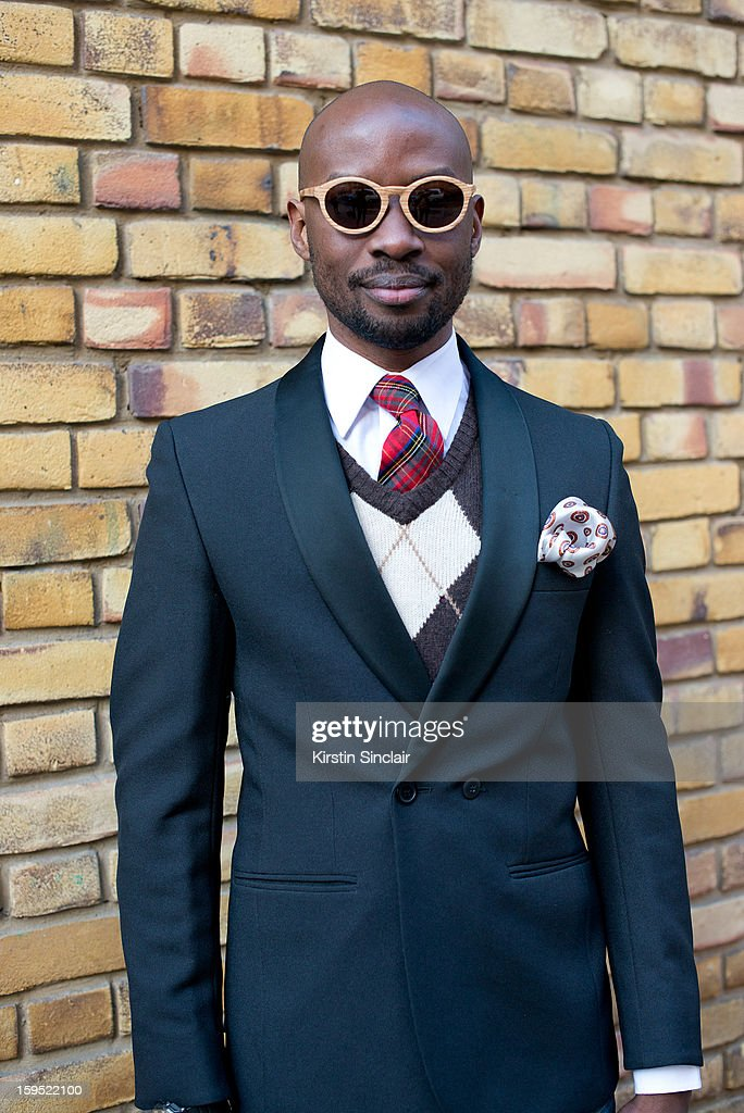 David Nyanzi photographer wearing H and M sweater, a Dolce and Gabbana jacket, vintage tie and pocket scarf, Hugo Boss shirt and Finlay and Co sunglasses on day 3 of London Mens Fashion Week Autumn/Winter 2013, on January 09, 2013 in London, England.