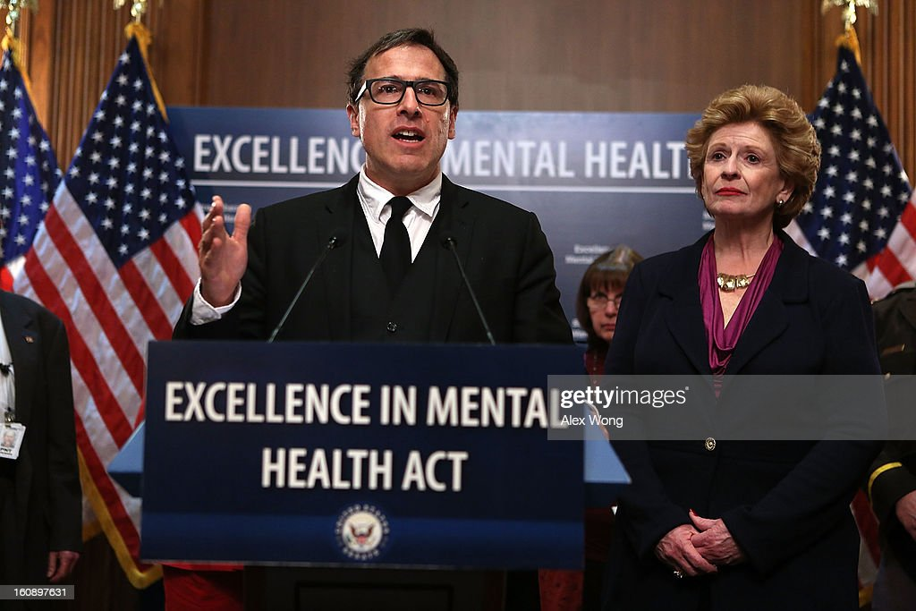David O. Russell, director of the film Silver Linings Playbook, speaks as U.S. Senator Debbie Stabenow (D-MI) looks on during a news conference February 7, 2013 on Capitol Hill in Washington, DC. A bipartisan group of senators will introduce the Excellence in Mental Health Act to help strengthen the nation's mental health services.