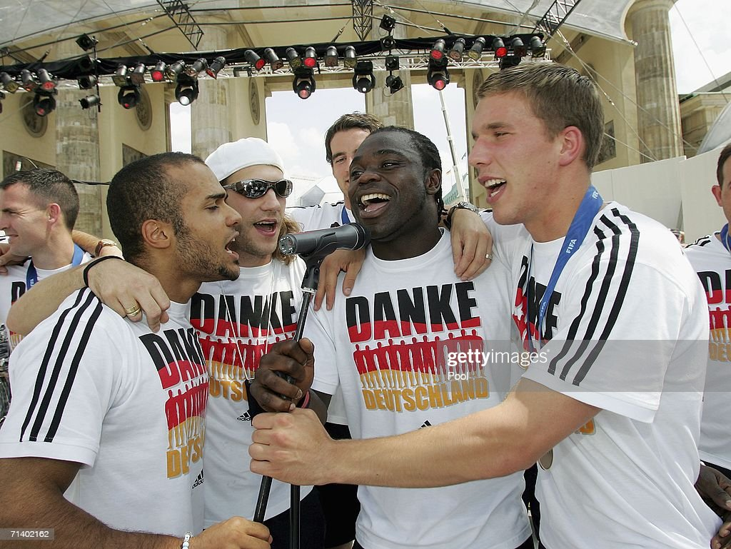David Odonkor, Torsten Frings, Gerald Asamoah and <a gi-track='captionPersonalityLinkClicked' href=/galleries/search?phrase=Lukas+Podolski&family=editorial&specificpeople=204460 ng-click='$event.stopPropagation()'>Lukas Podolski</a> sing at the fan mile at Brandenburger Tor on July 9, 2006 in Berlin, Germany.