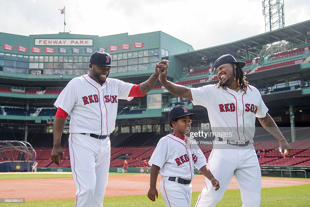 David Ortiz and Hanley Ramirez of the Boston Red Sox alongside his son Hansel high five before posing for the team photograph before a game against...