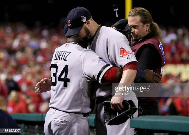 David Ortiz embraces Jon Lester of the Boston Red Sox as he returns to the dugout after being removed from the game in the eighth inning against the...
