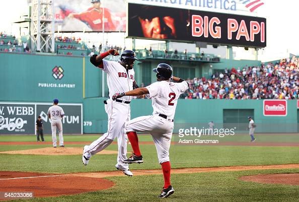 David Ortiz high fives Xander Bogaerts of the Boston Red Sox after hitting a tworun home run in the first inning during the game against the Texas...