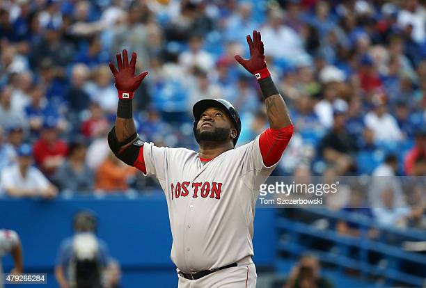 David Ortiz of the Boston Red Sox celebrates after hitting a threerun home run in the first inning during MLB game action against the Toronto Blue...