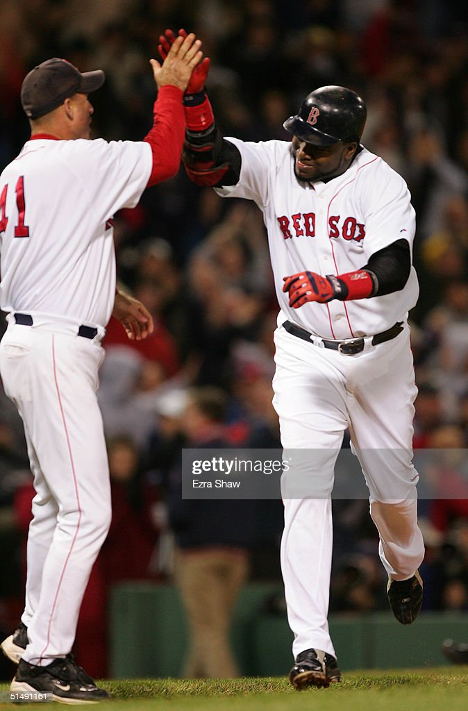 David Ortiz #34 of the Boston Red Sox celebrates with first base coach Dale Sveum #41 after hitting the game winning two-run home run to defeat the New York Yankees 6-4 in the twelth inning during the American League Championship Series on October 17, 2004 at Fenway Park in Boston, Massachusetts.