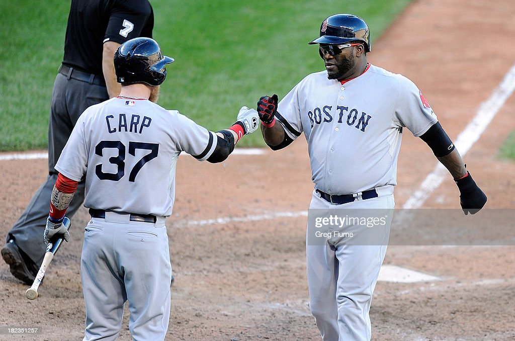 <a gi-track='captionPersonalityLinkClicked' href=/galleries/search?phrase=David+Ortiz&family=editorial&specificpeople=175825 ng-click='$event.stopPropagation()'>David Ortiz</a> #34 of the Boston Red Sox celebrates with Mike Carp #37 after scoring in the ninth inning against the Baltimore Orioles at Oriole Park at Camden Yards on September 29, 2013 in Baltimore, Maryland.