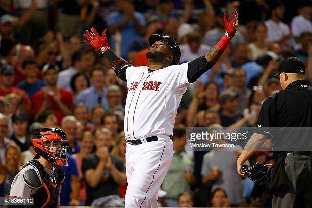 David Ortiz of the Boston Red Sox gestures at home plate as catcher Caleb Joseph of the Baltimore Orioles looks on after his tworun home run during...