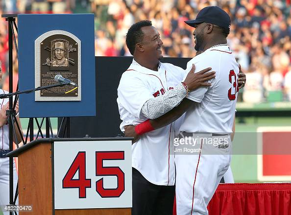 David Ortiz of the Boston Red Sox hugs Pedro Martinez a former member of the Boston Red Sox during a ceremony to retire Martinez's number 45 before a...