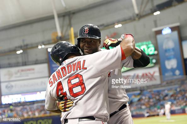 David Ortiz of the Boston Red Sox hugs teammate Pablo Sandoval as he makes his way back to the dugout after hitting his 499th career MLB home run off...