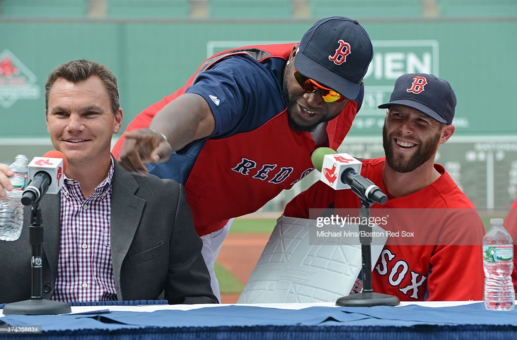 David Ortiz #34 of the Boston Red Sox interrupts a press conference announcing the signing of an eight year contract for Dustin Pedroia #15 by General Manager Ben Cherington to present the infielder with second base on July 24, 2013 at Fenway Park in Boston, Massachusetts.