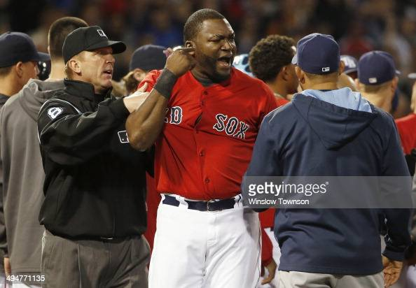 David Ortiz of the Boston Red Sox is contained by an unidentified Tampa Bay Ray and umpire Jeff Kellogg after teammate Mike Carp of the Boston Red...