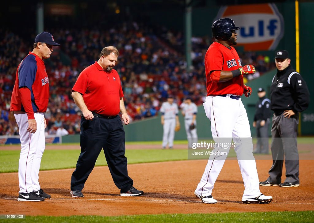David Ortiz #34 of the Boston Red Sox jogs in front of manager John Farrell #53 and the medical staff after injuring himself on his run to first base in the fifth inning against the Detroit Tigers during the game at Fenway Park on May 16, 2014 in Boston, Massachusetts.
