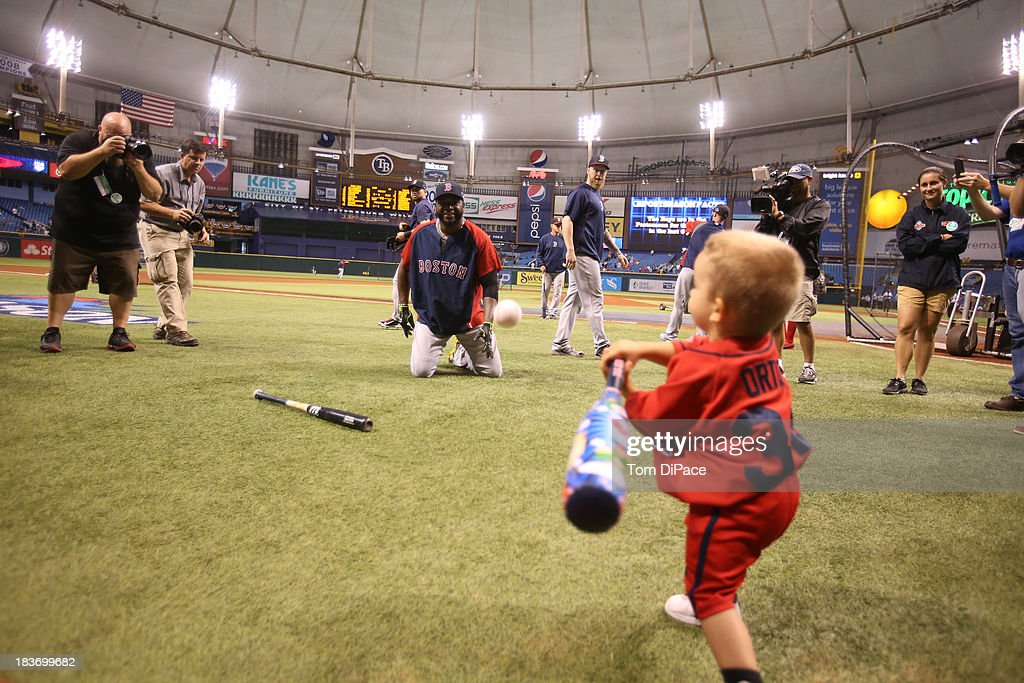 David Ortiz #34 of the Boston Red Sox pitches to a young Boston Red Sox fan wearing a David Ortiz jersey during batting practice before Game 4 of the American League Division Series against the Tampa Bay Rays on Monday, October 8, 2013 at Tropicana Field in St. Petersburg, FL.