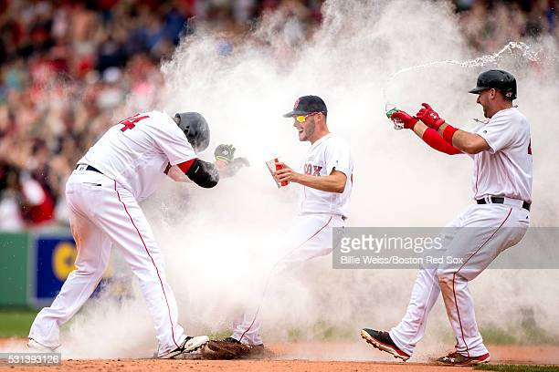 David Ortiz of the Boston Red Sox reacts as he is mobbed by Joe Kelly and Travis Shaw after hitting a game winning walkoff single during the eleventh...