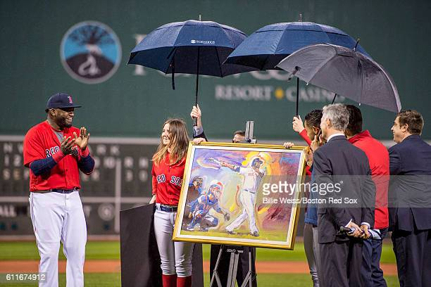 David Ortiz of the Boston Red Sox reacts as he is presented with a painting by artist Peter Max during a retirement tribute ceremony before a game...