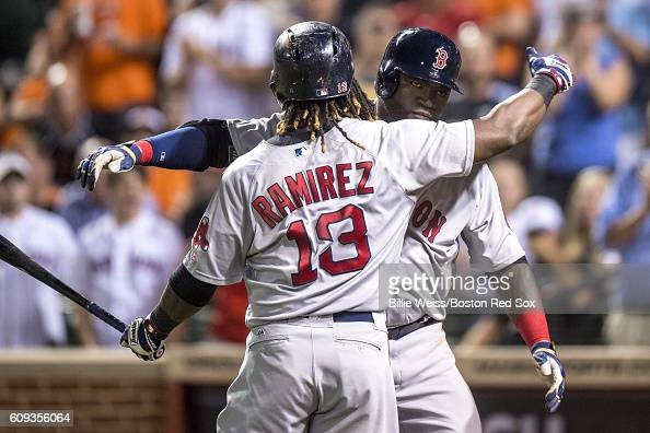 David Ortiz of the Boston Red Sox reacts with Hanley Ramirez after hitting a three run home run during the seventh inning of a game against the...