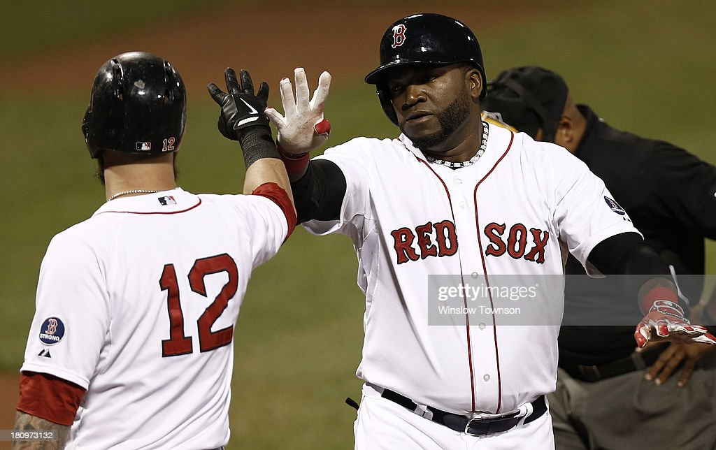 David Ortiz #34 of the Boston Red Sox, right, slaps hands with Mike Napoli #12 of the Boston Red Sox after his two-run home run against the Baltimore Orioles during the first inning of the game at Fenway Park on September 18, 2013 in Boston, Massachusetts.