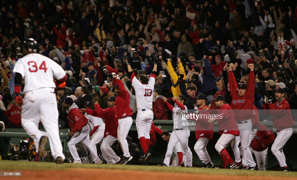 David Ortiz #34 of the Boston Red Sox runs to first base as the dugout celebrates his game winning two-run home run in the twelth inning to defeat the New York Yankees 6-4 during game four of the American League Championship Series on October 17, 2004 at Fenway Park in Boston, Massachusetts.