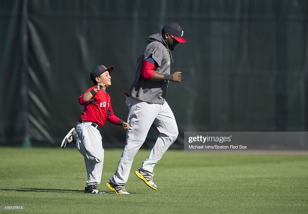 David Ortiz #34 of the Boston Red Sox runs with his son D'Angelo during a Spring Training workout at Fenway South on February 18, 2014 in Fort Myers, Florida.