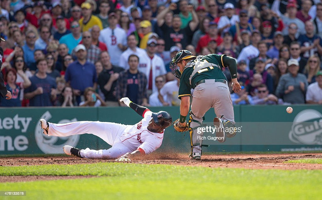 David Ortiz of the Boston Red Sox scores on a hit by teammate Mike Napoli as he avoids the tag by Stephen Vogt of the Oakland Athletics during the...