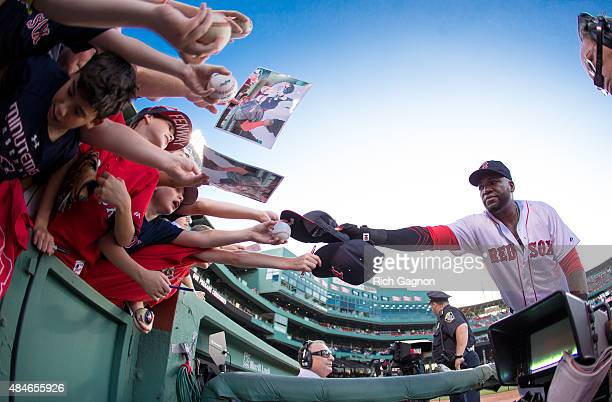 David Ortiz of the Boston Red Sox signs autographs for fans before a game against the Kansas City Royals at Fenway Park on August 20 2015 in Boston...