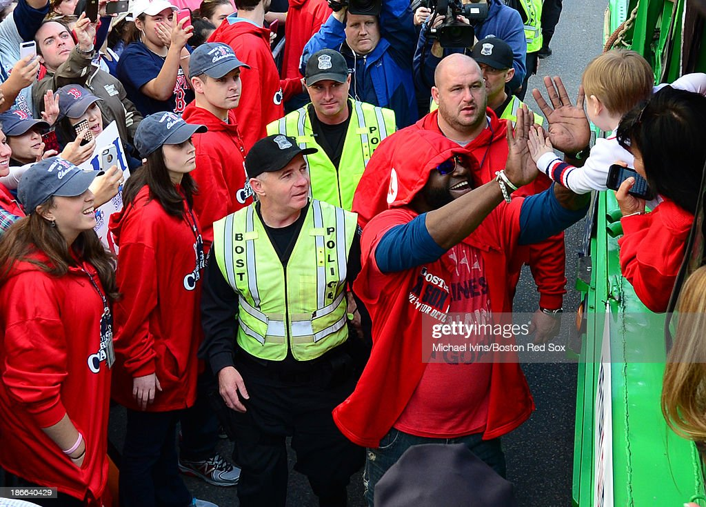 David Ortiz #34 of the Boston Red Sox waves to a fan during a victory parade on November 2, 2013 through Boston, Massachusetts.