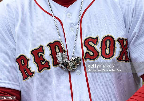 David Ortiz of the Boston Red Sox wears a necklace containing his 2004 2007 and 2013 championship rings along with a ring honoring his 2013 World...