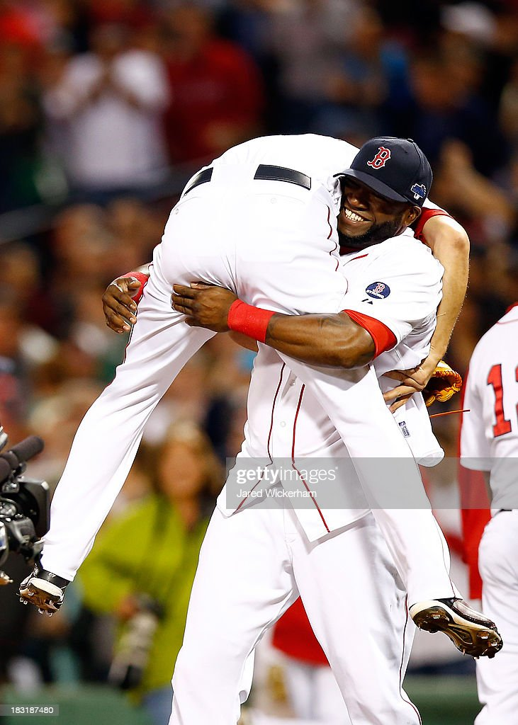 David Ortiz #34 picks up Koji Uehara #19 of the Boston Red Sox after defeating the Tampa Bay Rays 7-4 in Game Two of the American League Division Series at Fenway Park on October 5, 2013 in Boston, Massachusetts.