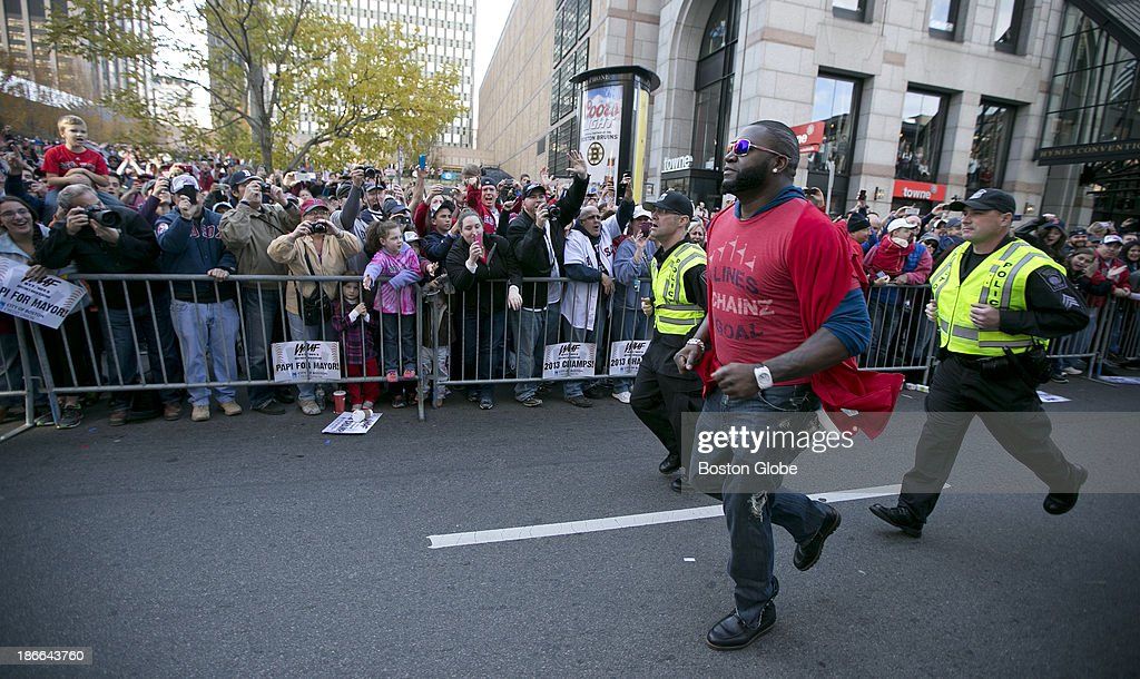 David Ortiz runs to the Boston Marathon finish line flanked by two Boston police officers as the Boston Red Sox celebrate their World Series victory with a Rolling Rally duck boat parade on Saturday, Nov. 2, 2013.