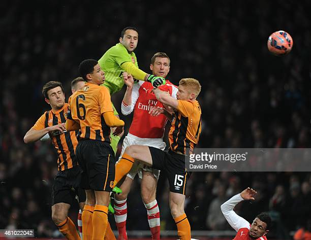 David Ospina of Arsenal punches the ball under pressure from Curtis Davies and Paul McShane of Hull during the match between Arsenal and Hull City in...