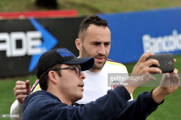 David Ospina of Colombia poses for a selfie photo with a fan during a training session at Headquarters of the Colombian Football Federation on March...
