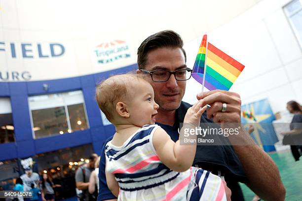David Ottersbach of Tampa hands his daughter Jolie a rainbow flag as they arrive at the Tampa Bay Rays' Pride Night game against the San Francisco...