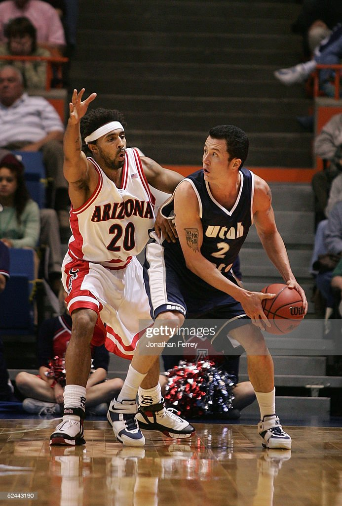 David Pak of the Utah State Aggies looks to pass under pressure from Salim Stoudamire of the Arizona Wildcats during the 2005 NCAA division 1 men's...
