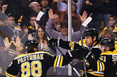 David Pastrnak and Ryan Spooner congratulate Milan Lucic of the Boston Bruins after he scored the game winning goal against the Florida Panthers...