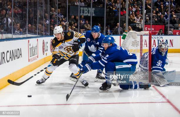 David Pastrnak of the Boston Bruins battles for the puck with Morgan Rielly Frederik Andersen and Ron Hainsey of the Toronto Maple Leafs during the...
