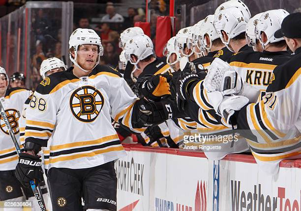 David Pastrnak of the Boston Bruins celebrates his first period goal against the Ottawa Senators with teammates at the players bench at Canadian Tire...
