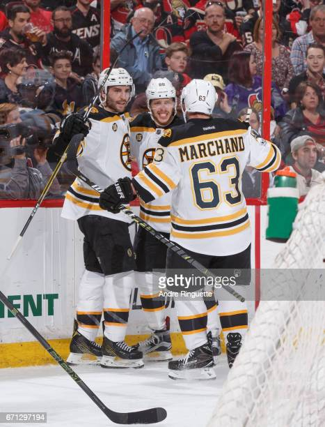 David Pastrnak of the Boston Bruins celebrates his second period goal against the Ottawa Senators with teammates Patrice Bergeron and Brad Marchand...