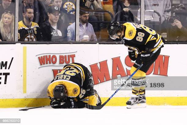 David Pastrnak of the Boston Bruins checks on Brandon Carlo after an injury during the first period against the Washington Capitals at TD Garden on...