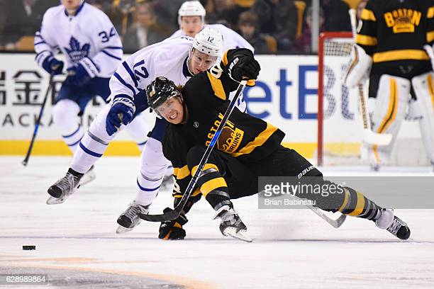 David Pastrnak of the Boston Bruins fight for the puck against Connor Carrick of the Toronto Maple Leafs at the TD Garden on December 10 2016 in...