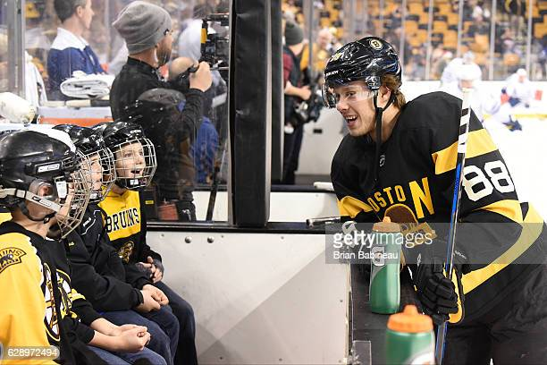 David Pastrnak of the Boston Bruins says hi to the bench kids during warm ups before the game against the Toronto Maple Leafs at the TD Garden on...