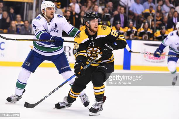David Pastrnak of the Boston Bruins skates against Christopher Tanev of the Vancouver Canucks at the TD Garden on October 19 2017 in Boston...