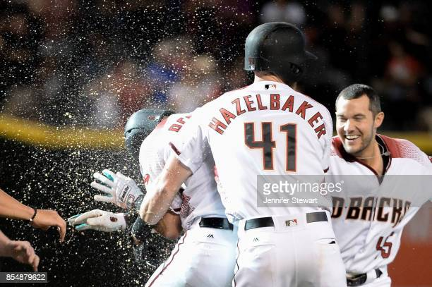 David Peralta of the Arizona Diamondbacks celebrates with Jeremy Hazelbaker and Kris Negron after drawing a bases loaded walk in the ninth inning to...