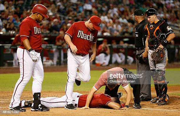 David Peralta of the Arizona Diamondbacks is looked at by Yasmany Tomas manager Chip Hale and a team trainer after being hit in the head by a pitch...