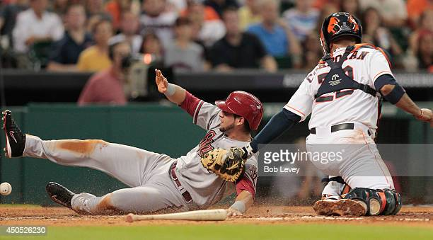 David Peralta of the Arizona Diamondbacks scores in the third inning as Carlos Corporan of the Houston Astros can't handle the throw at Minute Maid...