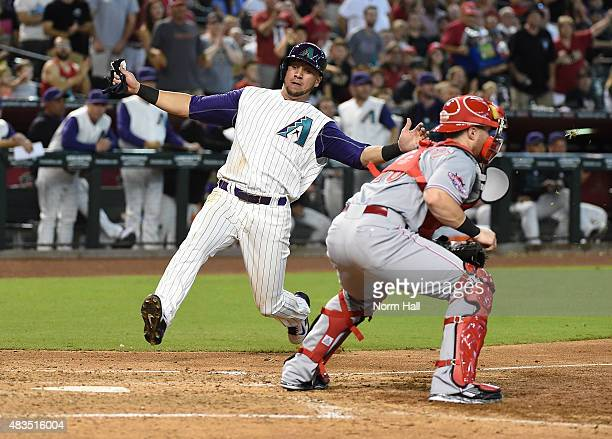 David Peralta of the Arizona Diamondbacks slides safely into home as Tucker Barnhart of the Cincinnati Reds waits for the throw during the fifth...